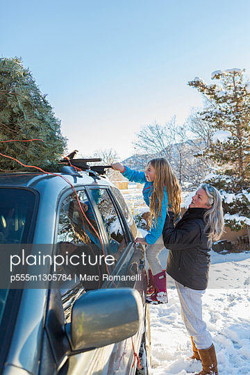 Caucasian mother and daughter hauling Christmas tree - p555m1305784 by Marc Romanelli