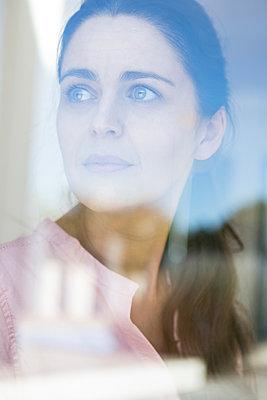 Frau blickt aus dem Fenster - p1156m2026934 von miep
