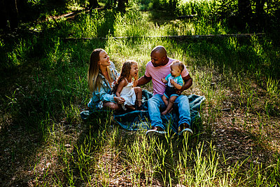 Young family laughing and giggling while sitting on the ground outside - p1166m2201868 by Cavan Images