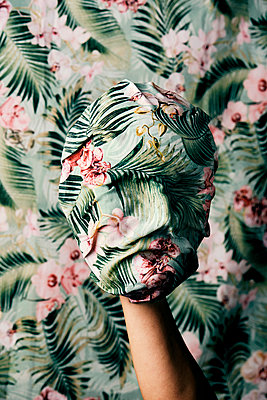 Playing with a floral-patterned mask against a floral-patterned background - p1423m2191556 by JUAN MOYANO