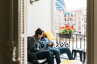 Two young professionals on office balcony, using their smartphones - p300m1460113 by Josep Rovirosa