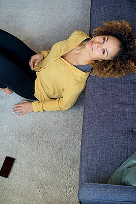 Portrait of smiling young woman leaning on couch at home - p300m1535314 by harry + lidy