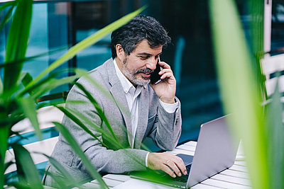 Mature businessman talking on phone call while using laptop in cafe - p300m2240100 by Daniel González