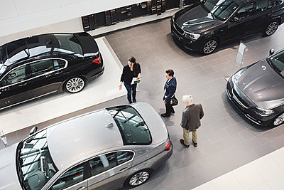 High angle view of saleswoman assisting customers at car showroom - p426m1143247 by Maskot