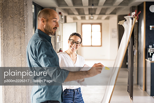 Smiling woman standing by man writing on canvas fabric at office - p300m2226317 by Robijn Page