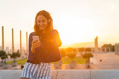Spain, Barcelona, Montjuic, smiling young woman with cell phone and headphones at sunset - p300m2058626 by VITTA GALLERY