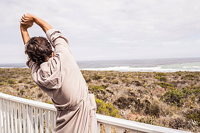 Man wearing bathrobe stretching on a terrace - p300m2167490 by Floco Images