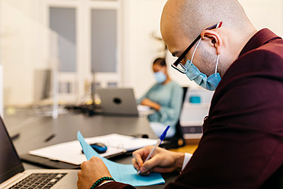 Businessman with safety mask writing while working at office desk - p300m2226688 by Josep Rovirosa