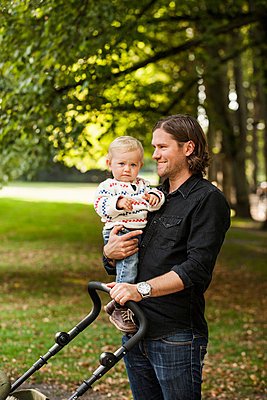 Smiling man holding baby carriage while carrying daughter in park - p426m977507f by Astrakan