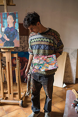 Male artist holding palette in artists studio - p429m1547678 by Arno Images