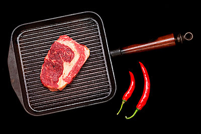 Meat in grill pan with chili peppers - p429m768216 by jf