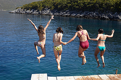 Four girls jumping from pier into the sea - p429m911444f by Tim Hall