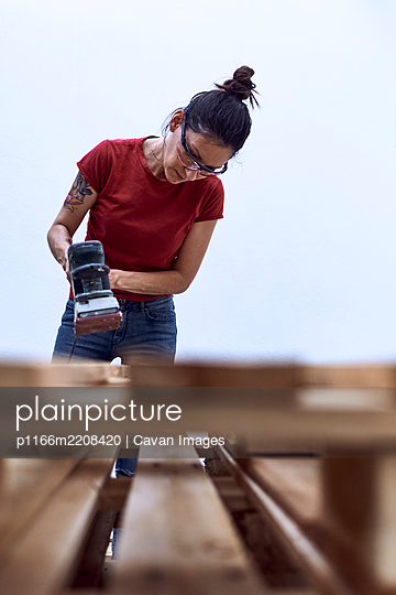 Young woman polishing a wooden plank with a power sander - p1166m2208420 by Cavan Images