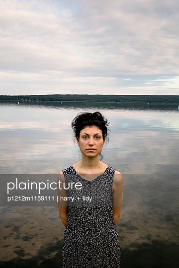 Portrait einer jungen Frau am Ufer - p1212m1159111 von harry + lidy