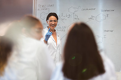 Smiling female science teacher leading lesson at whiteboard in classroom - p1023m2187389 by Martin Barraud