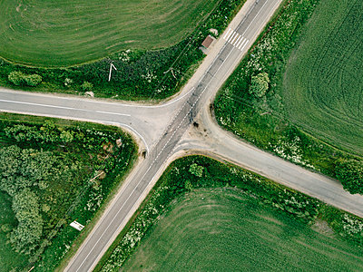 Aerial view of empty road amidst agricultural field - p1166m2025348 by Cavan Images
