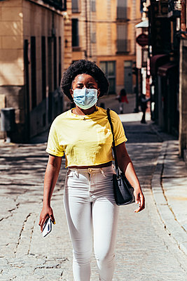 Black Afro-American girl with face mask walking down a city street. - p1166m2269117 by Cavan Images