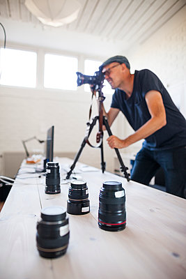 Mid adult photographer using SLR camera while various lenses on table in studio - p1264m1089050f by Astrakan