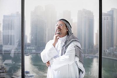 Middle Eastern businessman in office thinking about the future - p300m1120482f by zerocreatives