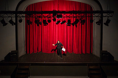Rehearsing actor with script standing on theatre stage in front of red curtain - p300m2103314 by Francesco Buttitta