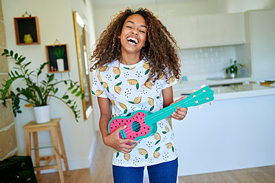 Laughing afro young woman with eyes closed holding ukulele in living room - p300m2243054 by Kiko Jimenez