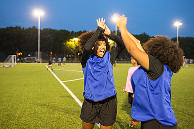 Female football players jubilant, Hackney, East London, UK - p429m1504760 by Ben Pipe Photography