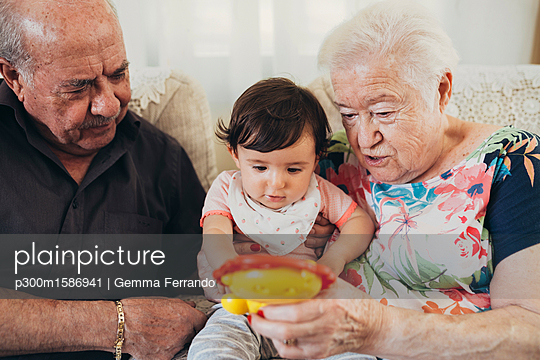 Great-grandparents sitting with baby girl on the couch at home looking at toy - p300m1586941 von Gemma Ferrando