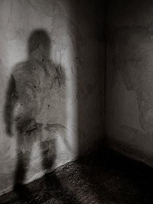 Shadow of a man with knife against bare concrete wall - p1280m2184510 by Dave Wall
