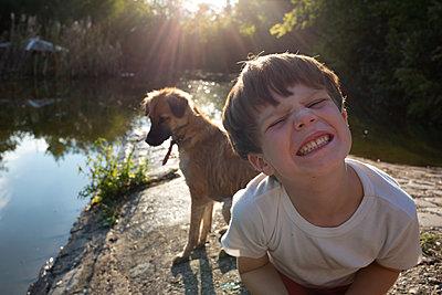 Junge mit Hund am Teich - p1308m2222813 von felice douglas