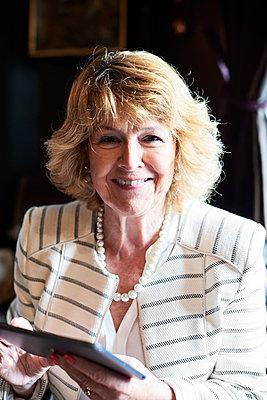 Portrait of smiling senior businesswoman holding tablet - p300m1499655 by Ivan Gener Garcia