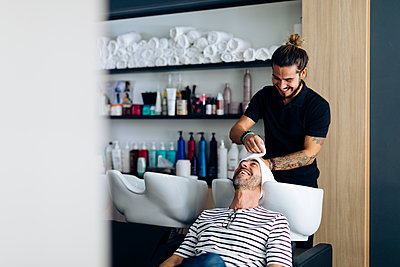 Hairdresser wrapped towel on client's hair at salon - p300m2203119 by Sofie Delauw
