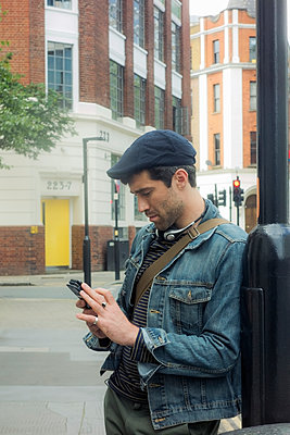 Mid adult man using mobile phone while leaning on pole at city - p300m2225049 by LOUIS CHRISTIAN
