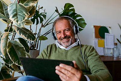 Mature men wearing headphones while using digital tablet at home - p300m2227247 by Valentina Barreto