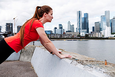 Active sportswoman doing warm up exercise over retaining wall in city - p300m2287368 by Angel Santana Garcia
