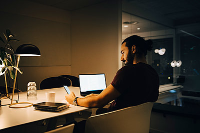 Male entrepreneur using smart phone while sitting with laptop at illuminated desk working late in office - p426m2194873 by Maskot