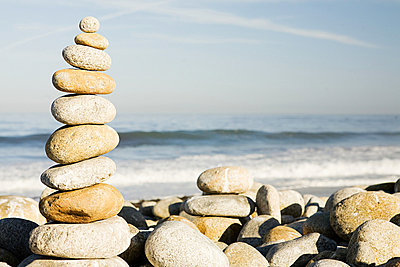 Stacked pebbles by the ocean - p9246669f by Image Source
