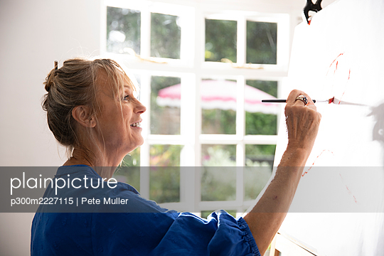 Senior woman painting picture on canvas at home - p300m2227115 by Pete Muller