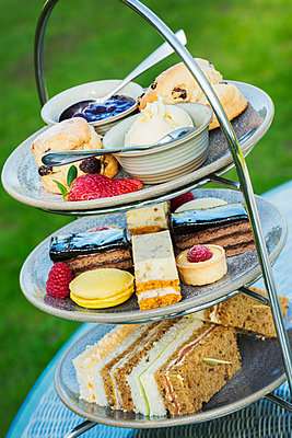 Close up of a cake stand with a selection of cakes and sandwiches, traditional afternoon tea.  - p1100m1450818 by Mint Images