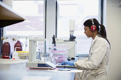 Scientist with headphones working at laptop in laboratory - p1192m1145641 by Hero Images