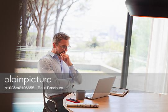 Businessman using laptop, working from home - p1023m2196655 by Paul Bradbury