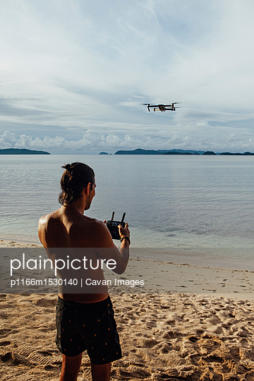 Shirtless man flying drone while standing at beach - p1166m1530140 by Cavan Images