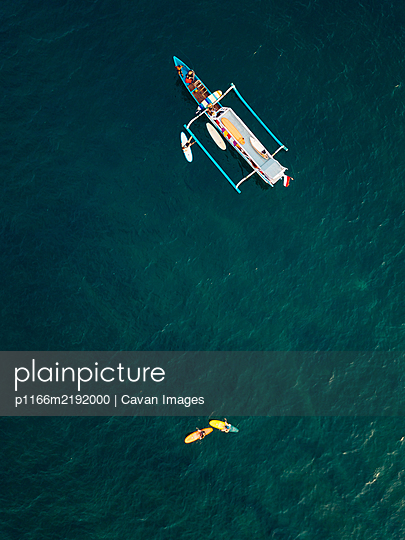 Aerial view of surfers and boat in the ocean, Lombok, Indonesia - p1166m2192000 by Cavan Images