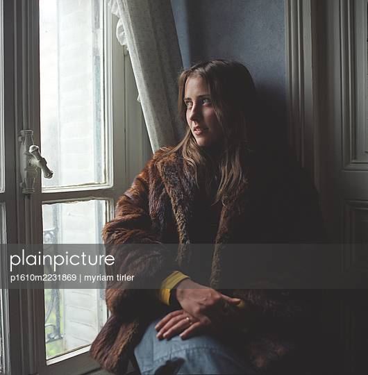 A woman by a window - p1610m2231869 by myriam tirler