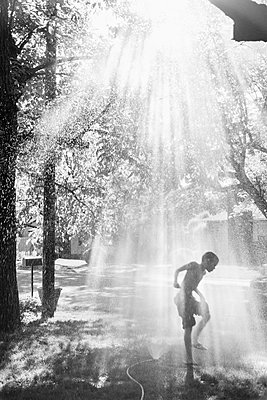 Child Playing in Sprinkler - p1262m1083621 by Maryanne Gobble