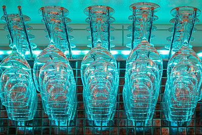 Glasses hanging upside down in bar - p1418m2141922 by Jan Håkan Dahlström