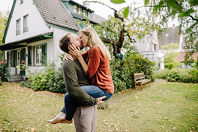 Happy couple kissing in garden, in front of their dream house - p300m2167271 by Kniel Synnatzschke