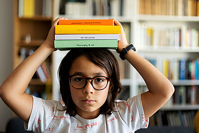 Portrait of serious boy with stack of books on his head - p300m2199573 by Valentina Barreto