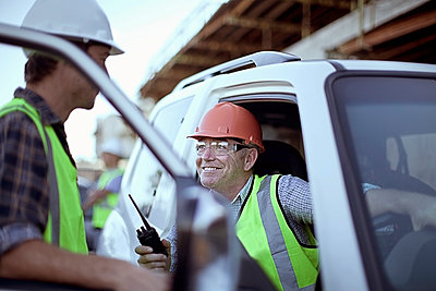 Two male construction workers chatting by car - p300m2264598 by LOUIS CHRISTIAN