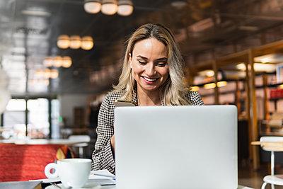 Smiling female freelancer working at cafe - p300m2286907 by NOVELLIMAGE