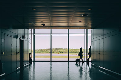 Full length of silhouette female business colleagues walking in corridor at airport - p426m2074467 by Maskot
